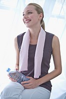 Young woman holding water bottle, towel around neck, portrait