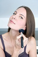 Young woman using make_up brush, portrait, close up