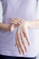 Woman applying cream to hands, close_up