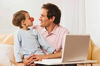 Father and son 4_5 at laptop, boy wearing clown nose