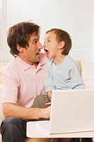 Father and son 4_5 at laptop, making a face