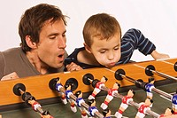 Germany, Father and son 4_5 playing tabletop soccer