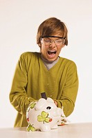 Teenage boy 13_14 smashing piggy bank with hammer