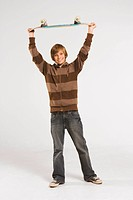 Teenage boy 13_14 holding skateboard over head, smiling