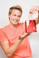 Young man holding small shopping bag, portrait