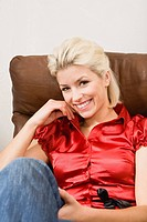 Young woman relaxing on chair, smiling, portrait, close_up