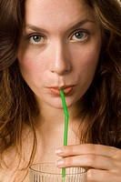 Young woman drinking through straw, close up