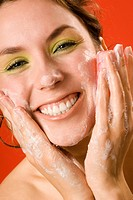 Young woman washing face with cake of soap, close up