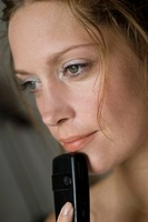 Young woman holding mobile phone, close up
