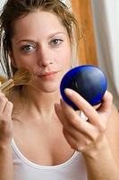 Young woman using make_up brush, close up