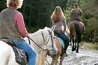 Austria, Salzburger Land, Altenmarkt, Young people horse riding, rear view