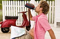 Man drinking from a water bottle beside his scooter