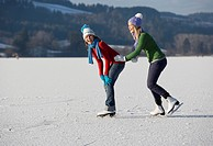 Austria, Salzkammergut, Lake Irrsee, Female teenagers 14_15 skating, having fun