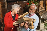 Austria, Karwendel, Senior couple carrying firewood, portrait