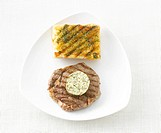 Steak, herb butter and baguette bread, elevated view