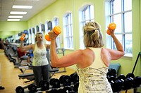 White woman with free weights in mirror in fitness center