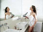 Woman in bathroom, drying her hair