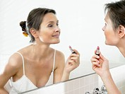 Woman in bathroom, applying makeup