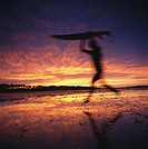 Surfer running on beach at sunset