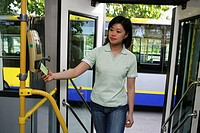 a chinese young woman paying bus fare with a bus card