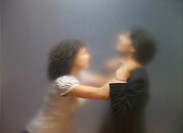 Blurred image of woman trying to strangle co_worker. Seen through frosted office screen.