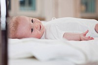A baby in white suit lying on a bed smiling