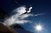 Skier jumping into the air with sun and snow trail.