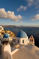 View of a Buildings in the Village of Oia perched on steep Cliffs overlooking the submerged Caldera, Santorini, Greece