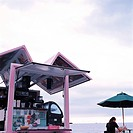 Coffee shop at beach, woman and umbrella in background
