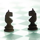 Two black wooden chess pieces on chess board
