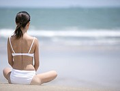 Young woman in bikini on beach sitting in yoga position, rear view