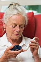 Elderly lady checking blood glucose level