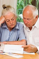 Elderly married couple reading pension award