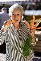 Older female person eating carrots