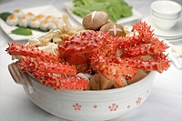 A cooked king crab in a white pot with hot pot ingredients under