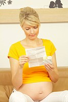 Pregnant woman reading instruction leaflet