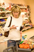 Female customer controlling receipt in the supermarket