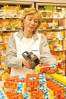 Female employee labeling goods in the supermarket