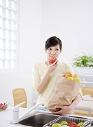 Young woman biting apple with bag of groceries on hand in kitchen
