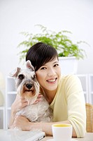 Close_up of young woman embracing Wire Fox Terrier at table, smiling