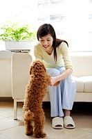 Young woman sitting on sofa, making Toy Poodle stand on two feet