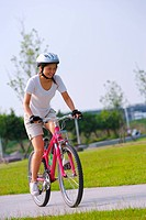 Young woman riding bicycle on road