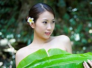 Naked young woman standing with banana leaf on breast, looking away, smiling