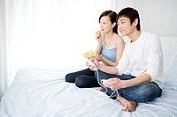Young couple sitting on bed watching TV, smiling, side view