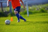 Person kicking soccer ball