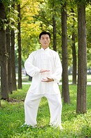 Man practicing Tai Chi amongst trees, portrait