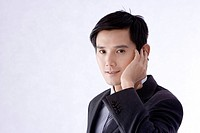 Young businessman touching his ear, side view, portrait