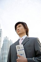 Young businessman standing with newspaper in hand, close_up