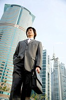 Businessman standing outdoors, low angle view