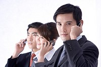 Young businesspeople in a row using cell phone